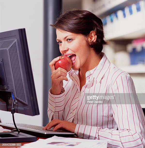 Young woman sitting at PC eating apple