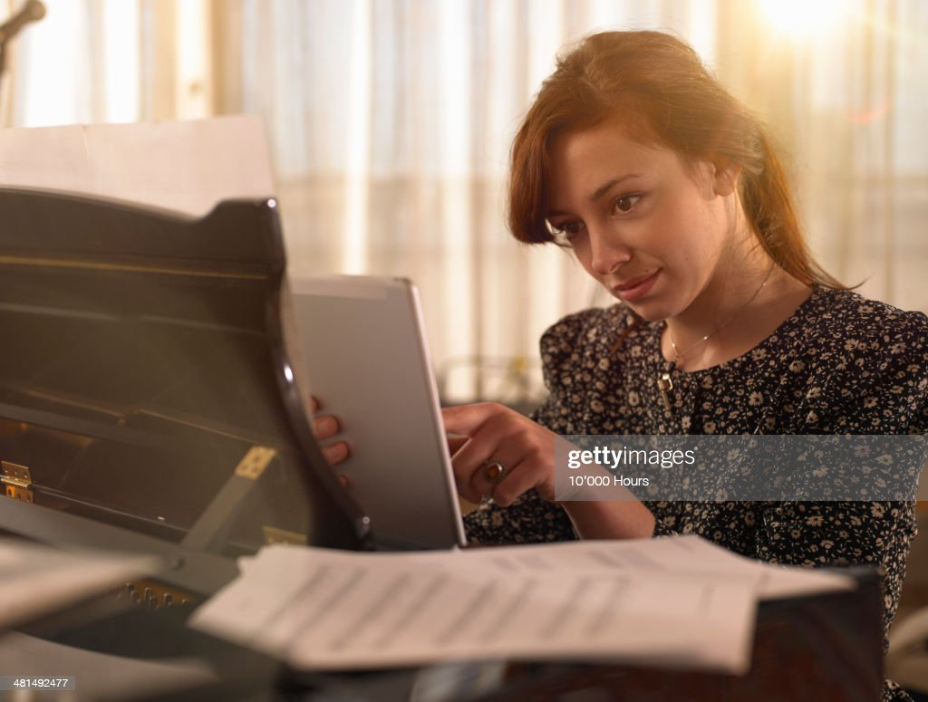 Young woman sitting at piano using tablet computer : ストックフォト