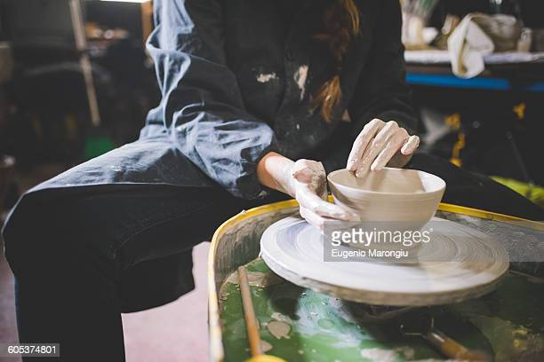 Young woman sitting at pottery wheel making clay pot