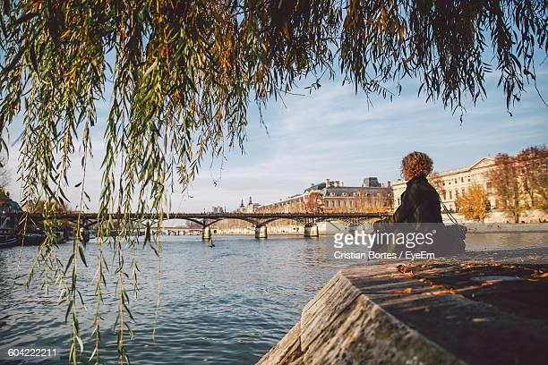 young woman sitting at seine riverbank with tree leaves on foreground - bortes stockfoto's en -beelden