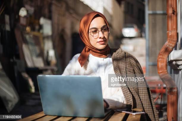 歩道カフェに座ってラップトップを使用している若い女性 - サウジアラビア ストックフォトと画像