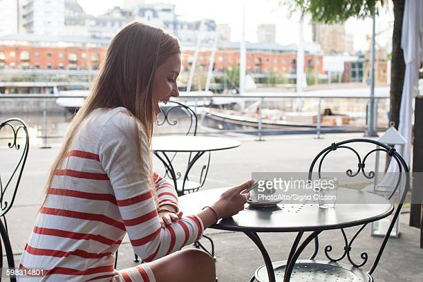 Young woman sitting at sidewalk cafe, laughing at smartphone