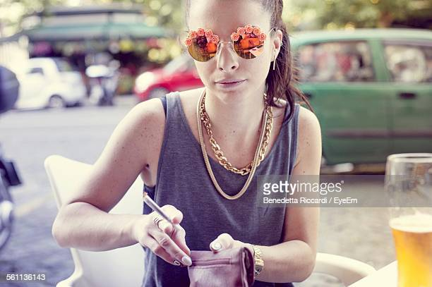 young woman sitting at sidewalk cafe - choker stock photos and pictures