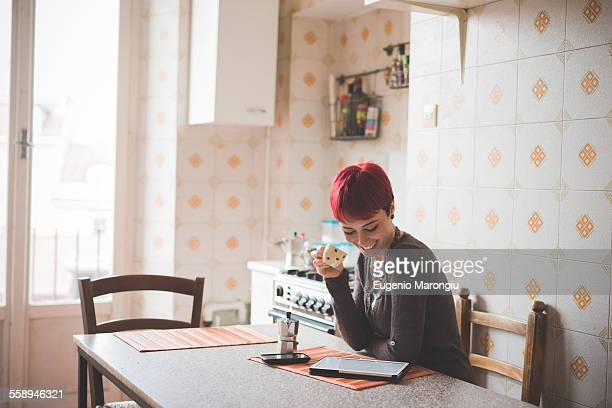 Young woman sitting at table drinking coffee, looking at digital tablet