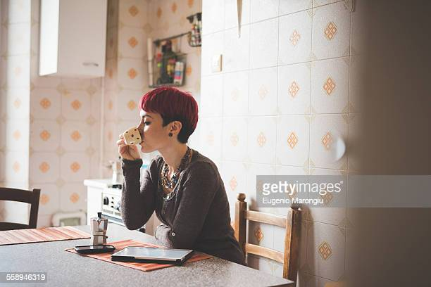 Young woman sitting at table drinking coffee