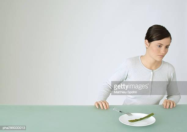 young woman sitting at table, in front of plate with single asparagus - paardenstaart haar naar achteren stockfoto's en -beelden