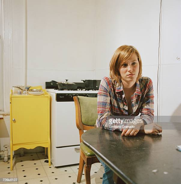 Young woman sitting at table in kitchen