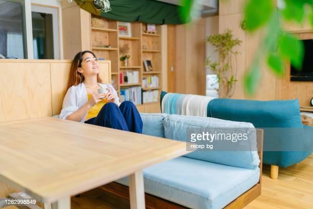 熱い飲み物を持って、彼女の時間を楽しんでリビングルームのテーブルに座って若い女性 - 心の平穏 ストックフォトと画像
