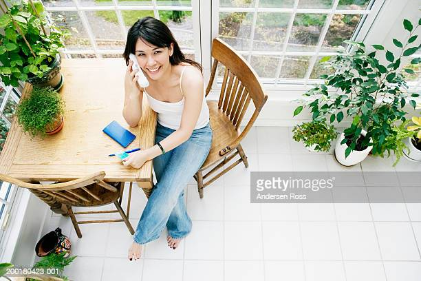 Young woman sitting at table, talking on phone, elevated view