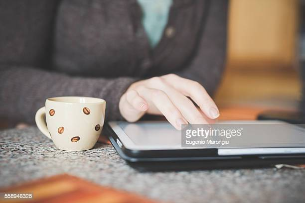 Young woman sitting at table using digital tablet, focus on hands