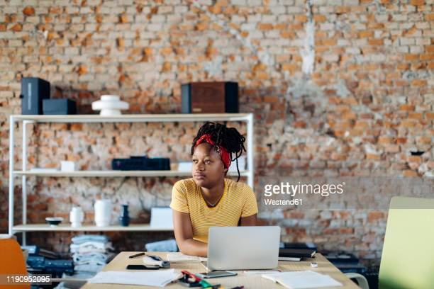 young woman sitting at table using laptop - oprichter stockfoto's en -beelden