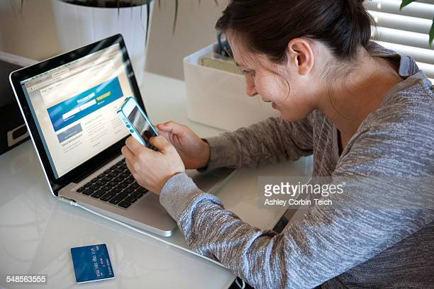 Young woman sitting at table using smart phone and laptop, credit card on table