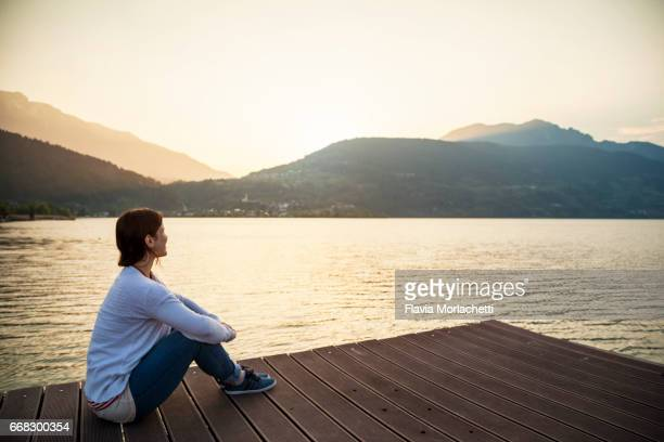 young woman sitting at the end of a dock over caldonazzo lake at sunset - zen like stock pictures, royalty-free photos & images