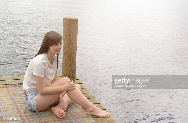 Young woman sitting at the end of a lakeside jetty