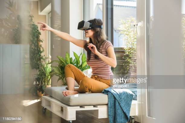 young woman sitting at the window at home wearing vr glasses - virtuelle realität stock-fotos und bilder