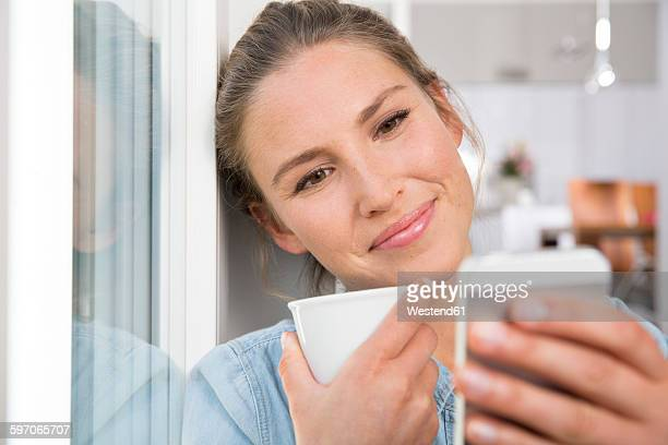 Young woman sitting at the window, drinking coffee an reading sms