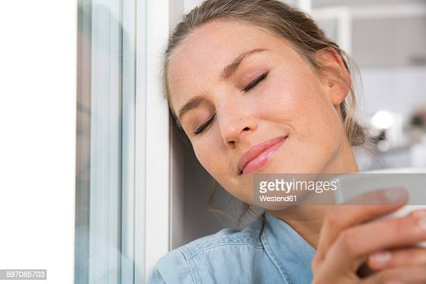 Young woman sitting at the window, drinking coffee