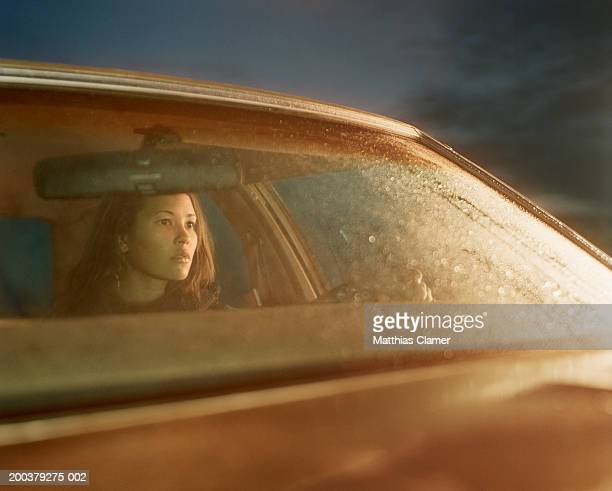 young woman sitting behind wheel of car, side view - rear view mirror stock pictures, royalty-free photos & images