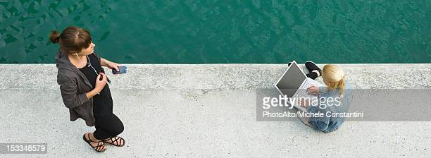 Young woman sitting beside canal, using laptop computer, elevated view