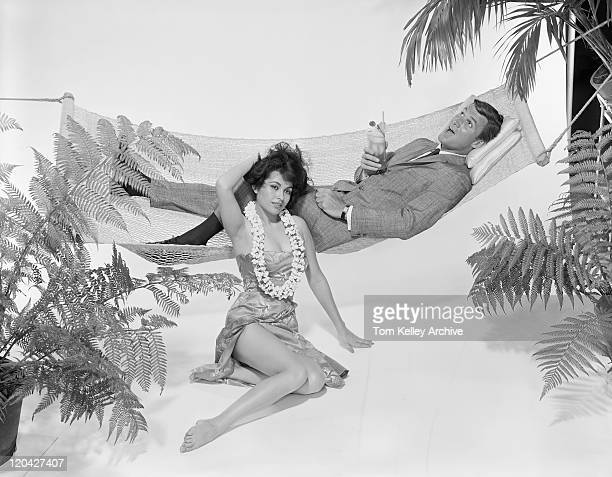 Young woman sitting beside man relaxing in hammock with drink