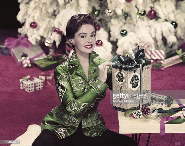 Young woman sitting besides christmas present, smiling, portrait