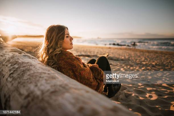 young woman sitting by a beach at sunset in winter - reflection stock pictures, royalty-free photos & images