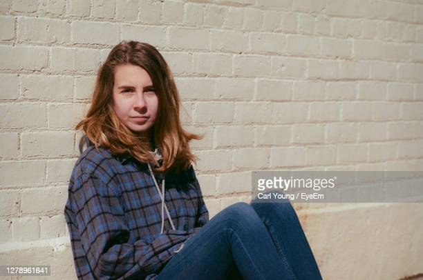 young woman sitting by a brick wall - homelessness stock pictures, royalty-free photos & images