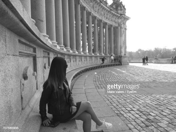 Young Woman Sitting By Colonnades At Buen Retiro Park
