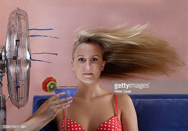 Young woman sitting by fan holding cocktail