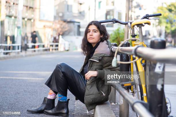 young woman sitting by her bike - mismatched clothes stock pictures, royalty-free photos & images