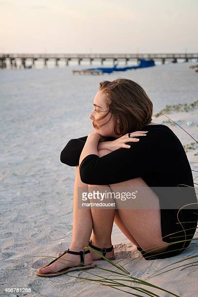 "young woman sitting by herself on the beach at sunset. - ""martine doucet"" or martinedoucet stock pictures, royalty-free photos & images"