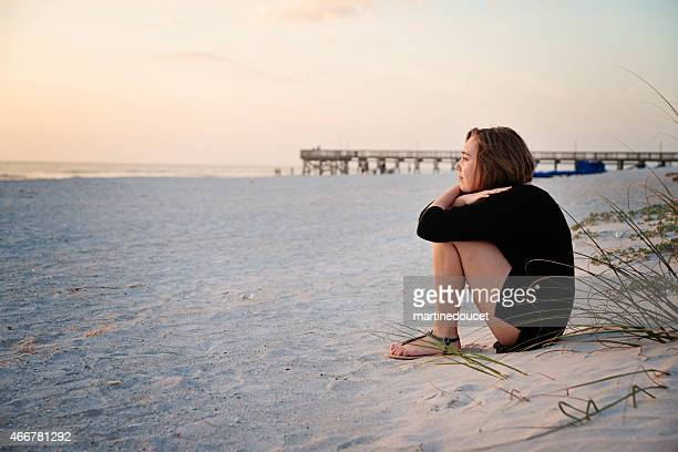 """junge frau sitzt mit sich selbst bei sonnenuntergang am strand. - """"martine doucet"""" or martinedoucet stock-fotos und bilder"""