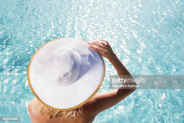 young woman sitting by pool wearing hat, rear view - sun hat stock pictures, royalty-free photos & images