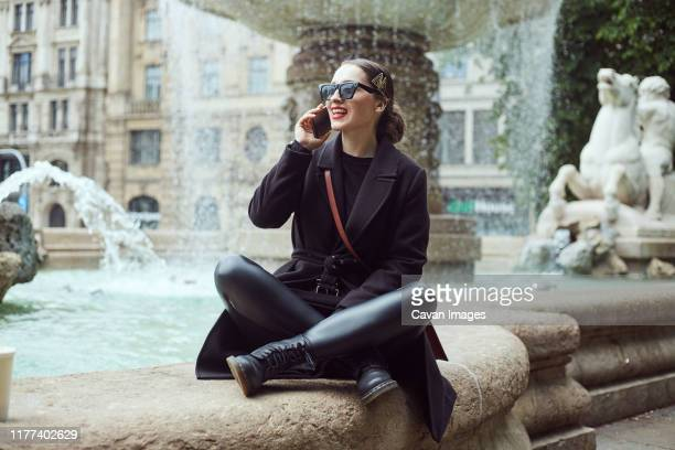 young woman sitting by the fountain and talking on the phone - leggings stock pictures, royalty-free photos & images