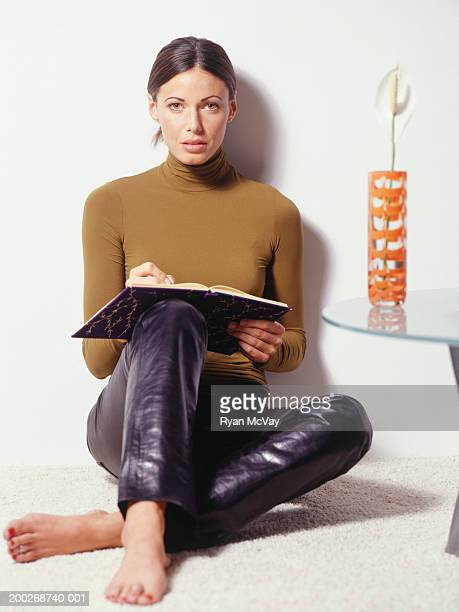 young woman sitting by wall, writing, - col roulé photos et images de collection