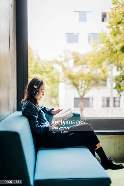 young woman sitting by window in library reading - campus stock pictures, royalty-free photos & images