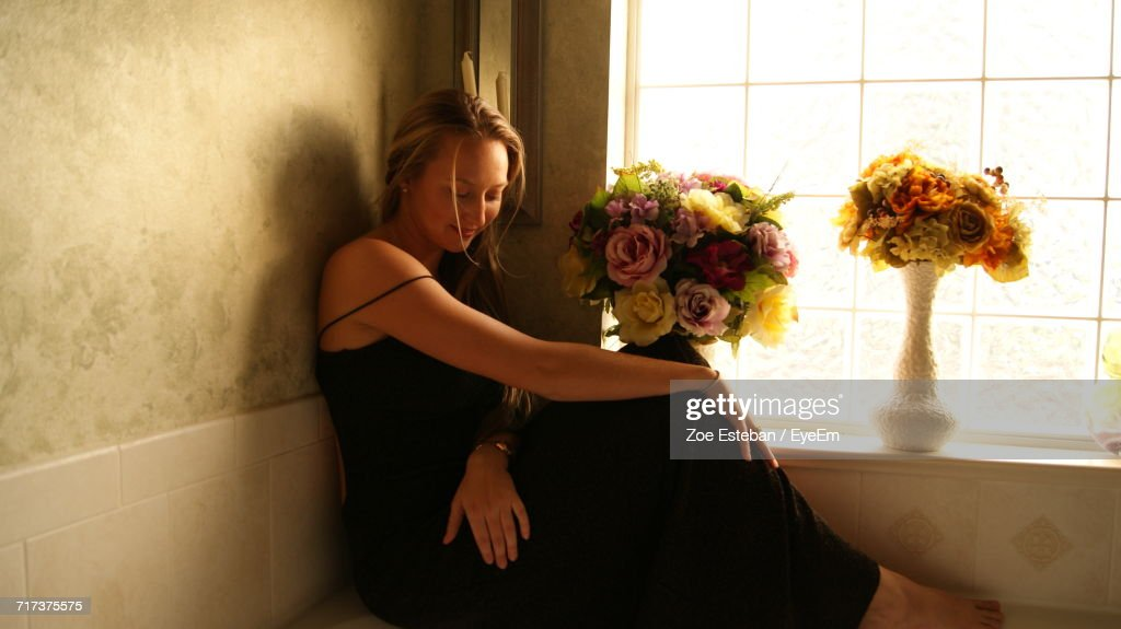 Young Woman Sitting By Window With Flower Vases At Home Stock Photo