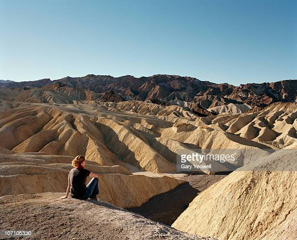 Young woman sitting by Zabriskie Point overlook