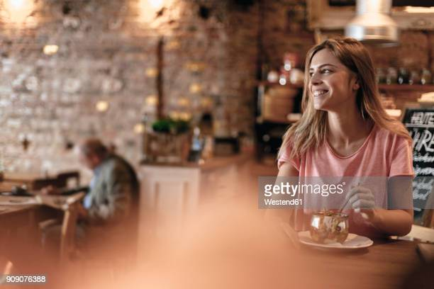Young woman sitting cafe, eating granola for breakfast
