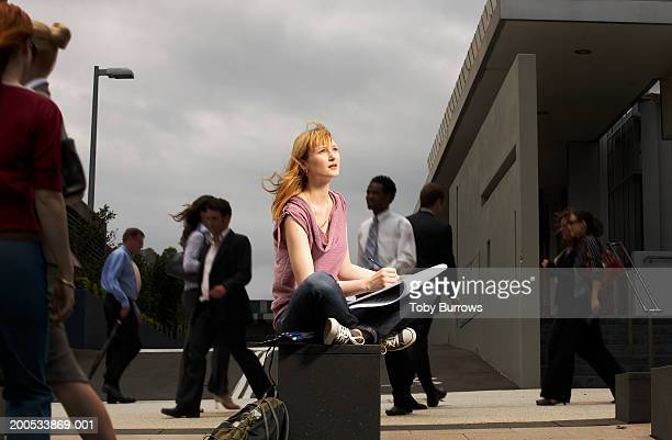 Young woman sitting cross legged in busy square with sketchpad