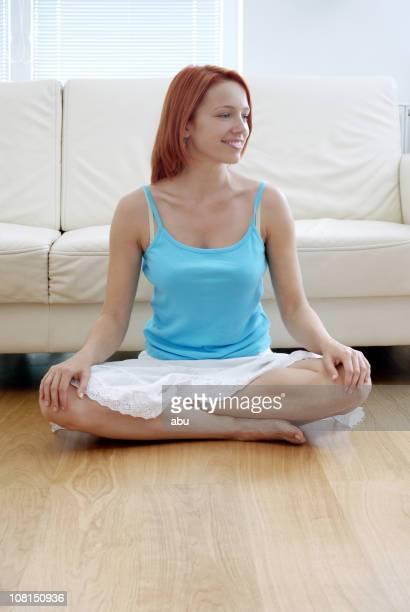 座る若い女性胡坐階にソファー、