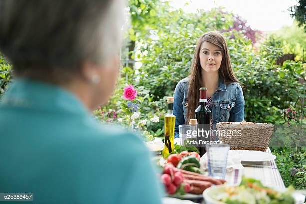 young woman sitting down for meal in garden - mensch im hintergrund stock-fotos und bilder
