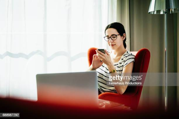 Young Woman Sitting Down Using Smartphone In Hotel Room