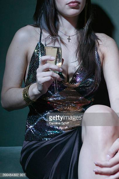 young woman sitting, holding champagne glass, mid section - schiff stock photos and pictures