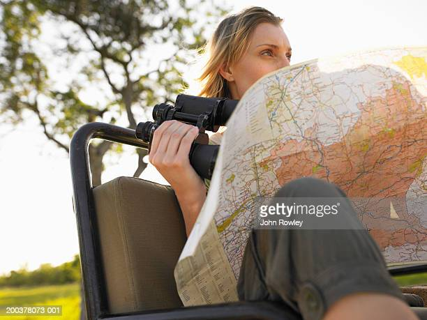 Young woman sitting in 4x4 holding binoculars and map, low angle view