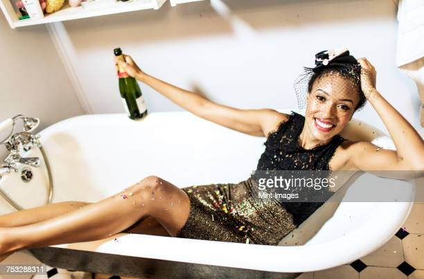 Young woman sitting in a bath holding a champagne bottle.