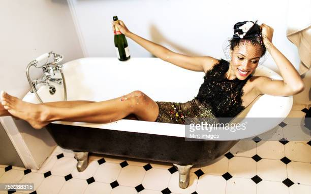 young woman sitting in a bath holding a champagne bottle. - cocktail dress stock pictures, royalty-free photos & images