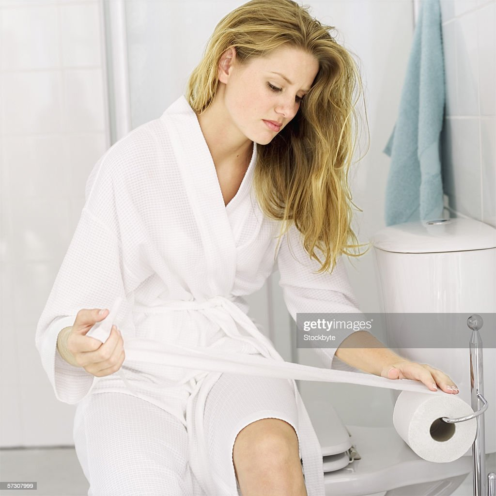 Young woman sitting in a bathroom taking toilet paper from a roll : Stock Photo