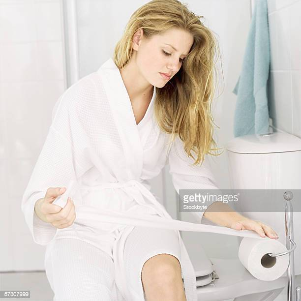 Young woman sitting in a bathroom taking toilet paper from a roll