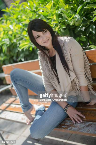 Young woman sitting in a bench with some plants behind her